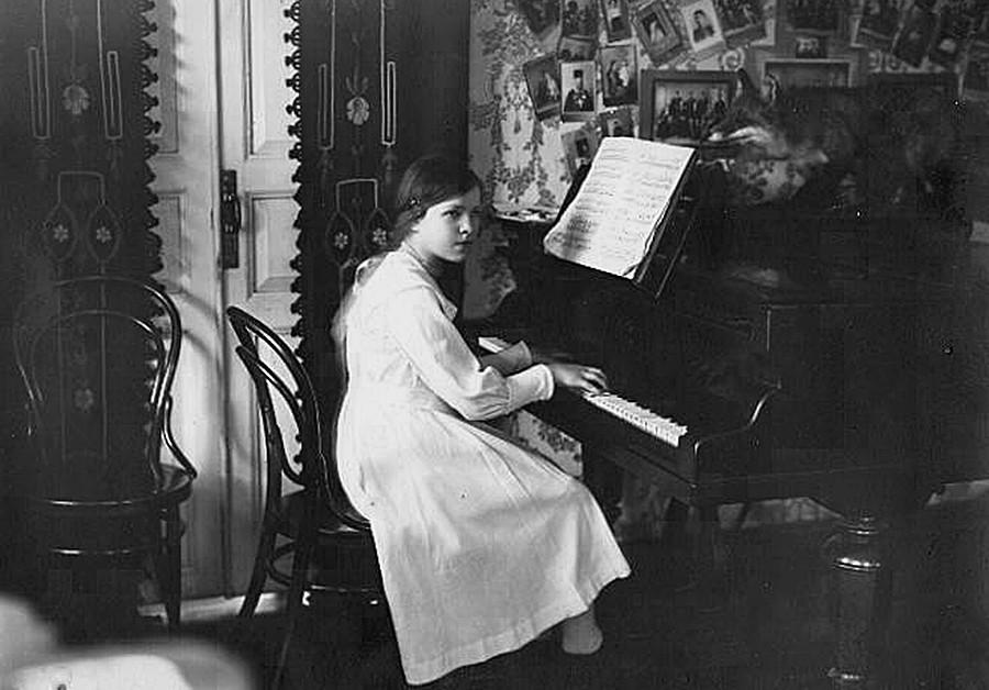 Seorang gadis memainkan piano di rumah.