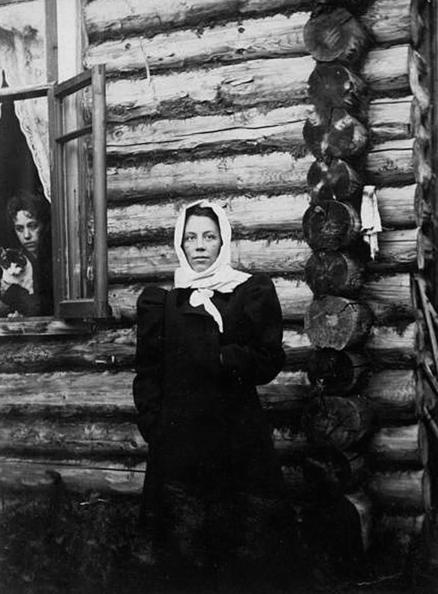 Seorang perempuan berdiri de depan rumah kayu.