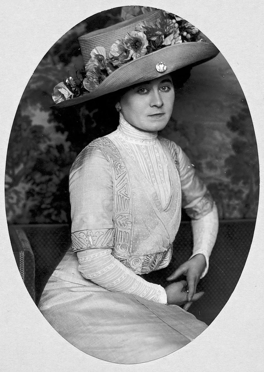 Potret seorang perempuan mengenakan topi.