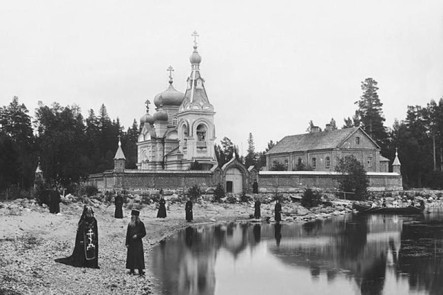 Un grupo de monjes y un schemnik junto a las celdas de Konevski, parte del monasterio de la Natividad en la orilla del lago Ladoga, 1892