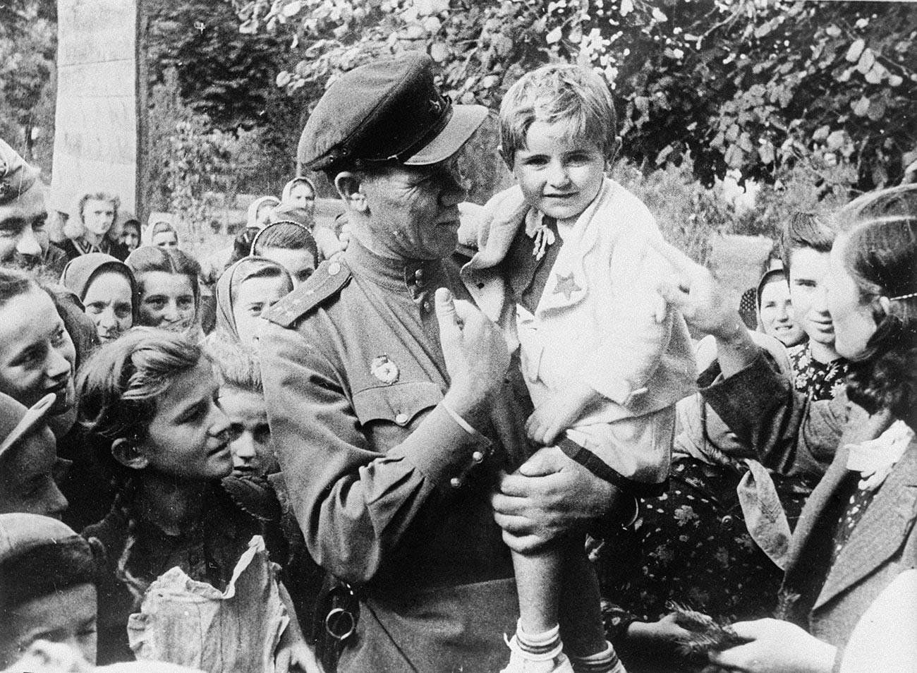 解放されたユーゴスラビアのオモリツァ村で子供を抱く赤軍親衛隊のセルゲイ・イワノフ大尉。1944年10月。