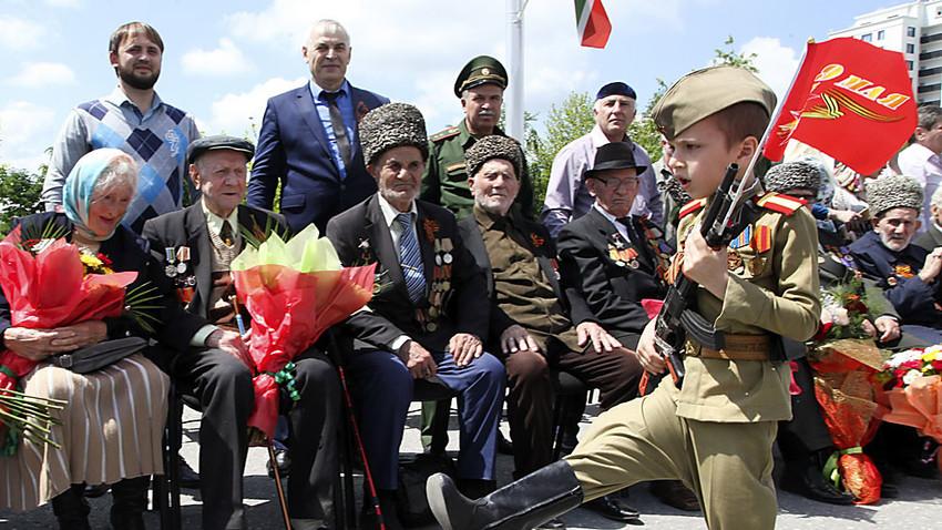 Чеченско момче, облечено в съветска военна униформа от времето на Втората световна война, марширува с флаг по време на празнуването на Деня на Победата в Грозни, столицата на Чечня.