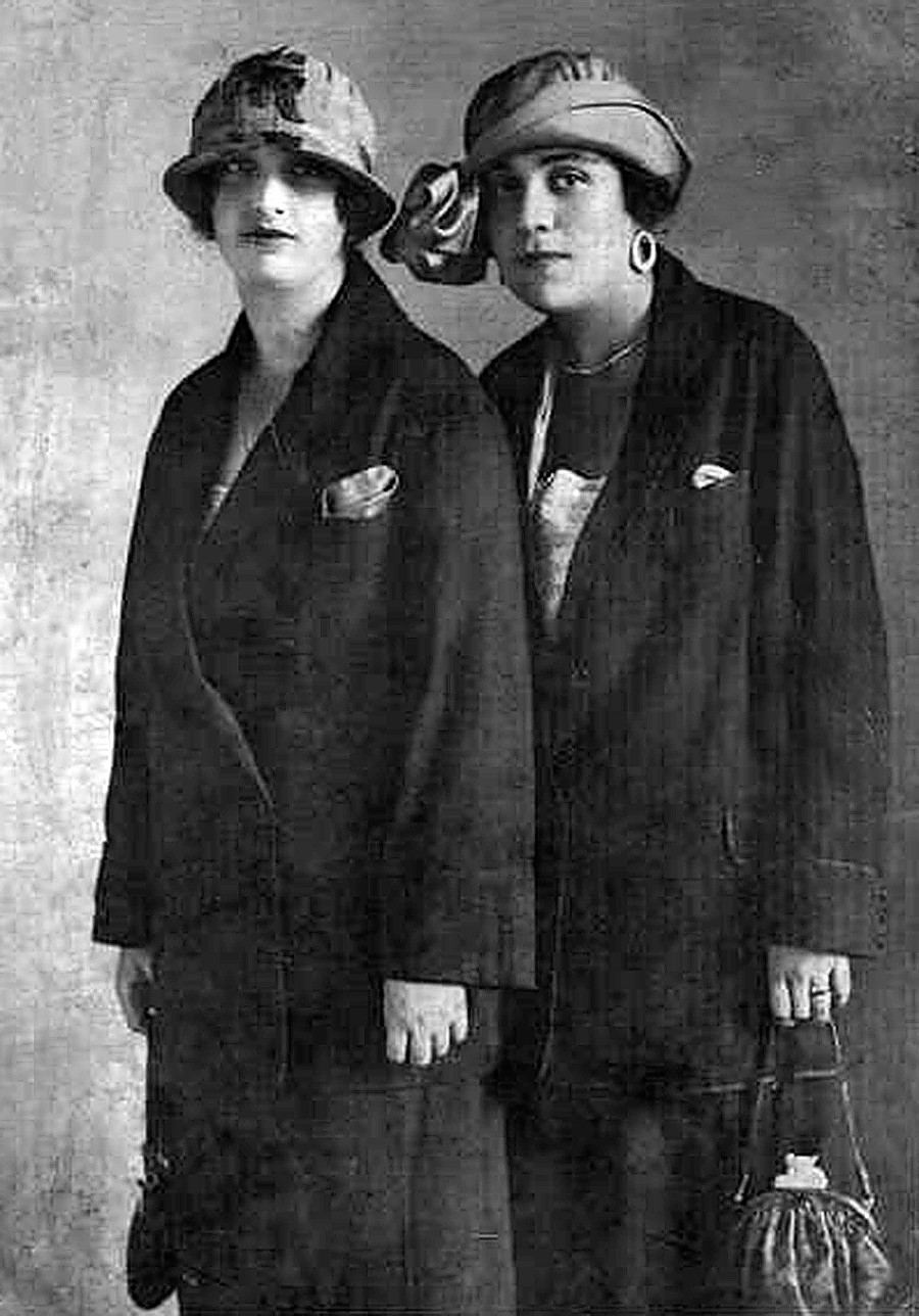Dua perempuan berpose dengan memakai topi.