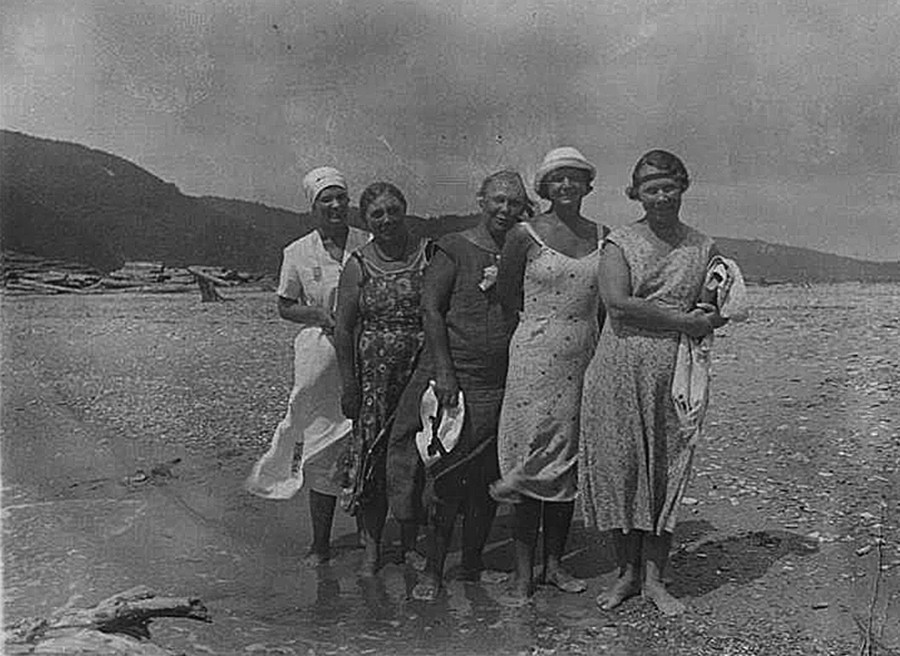 Lima perempuan berpose di tepi pantai.