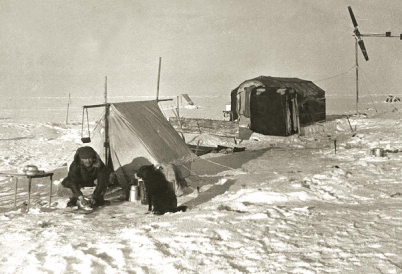 """Ернст Кренкељ, дежурен во кујната на станицата """"Северен пол"""". Покрај него е кучето Весели."""