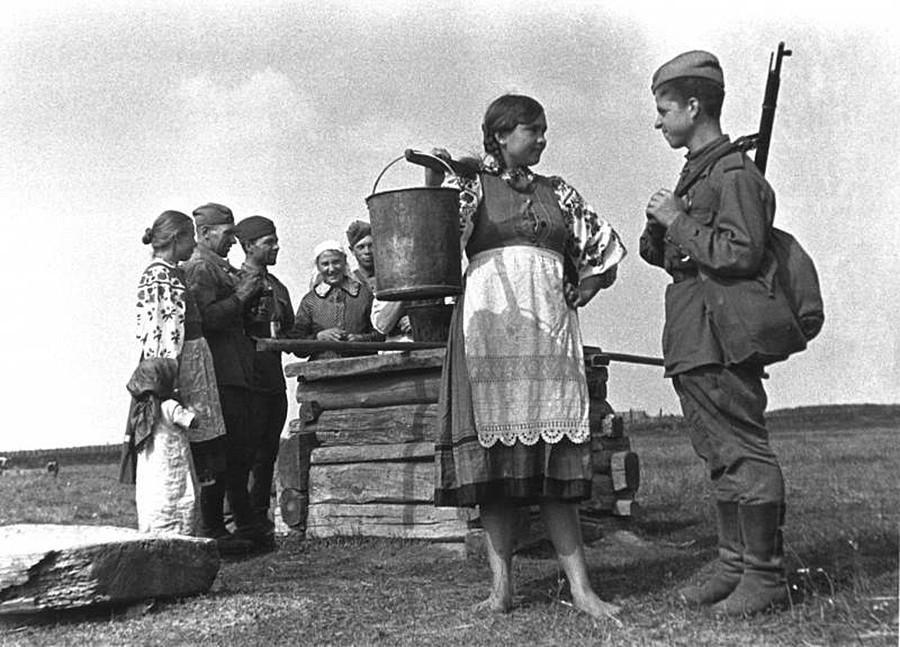 Ein junges Mädchen und ein Soldat an einem Brunnen