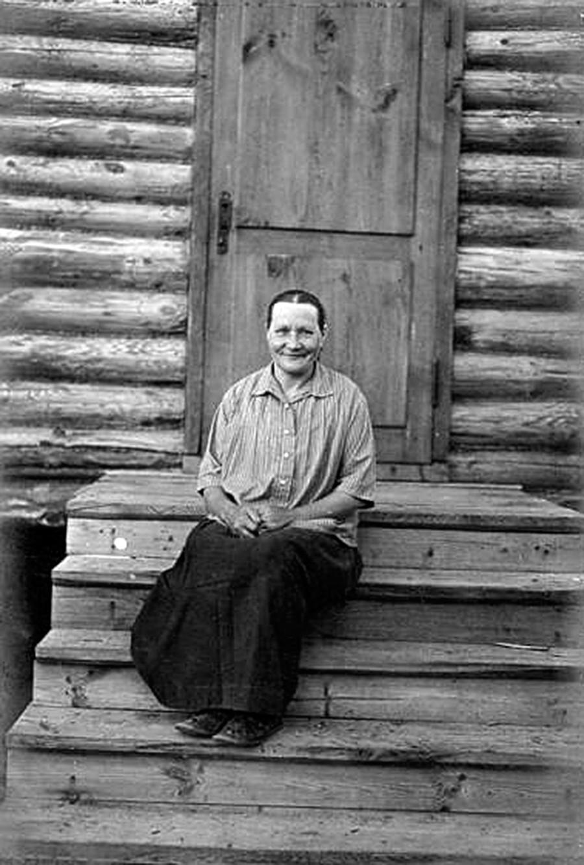 Retrato de mulher sentada à entrada de casa, em escada de madeira.