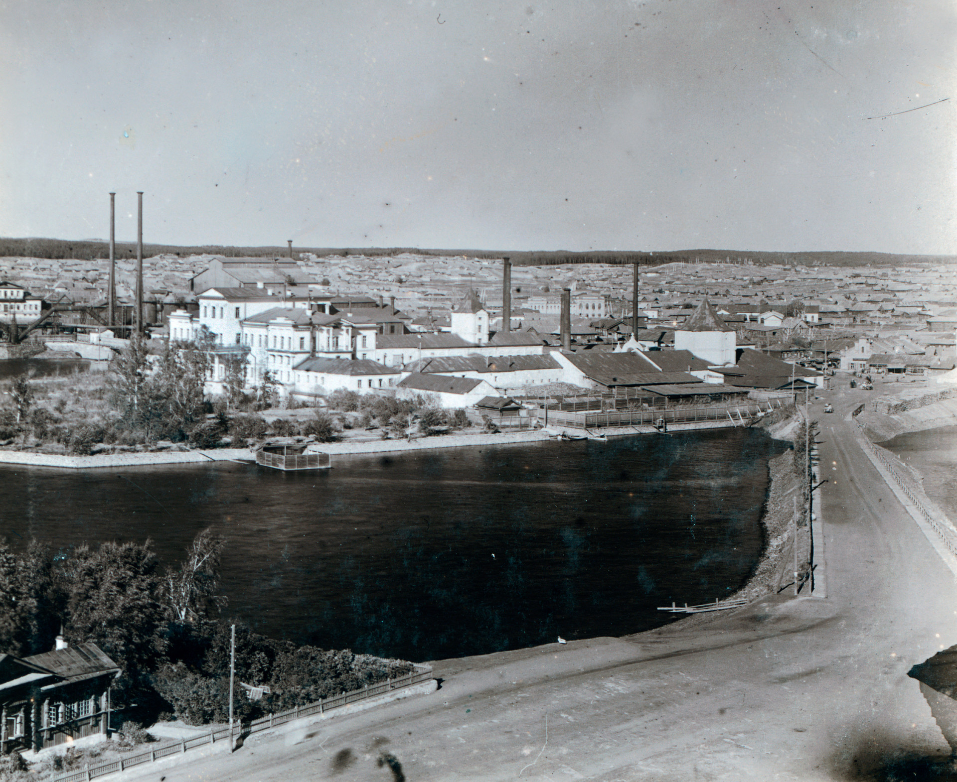 View of main Kyshtym factory with White House on former Demidov estate. Foreground: Town Pond (Kyshtym River). Right: 18th-century tower built by Nikita Demidov. 1909.