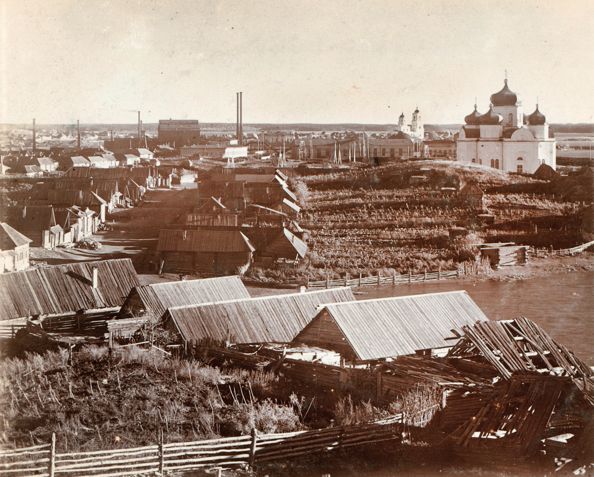 View of workers' houses & garden plots. Background: Kyshtym factory (left), Church of the Descent of the Holy Spirit, Cathedral of the Nativity of Christ. 1909.