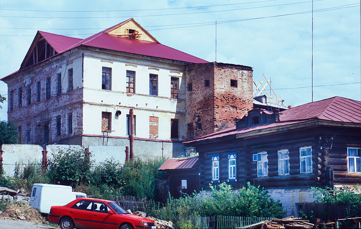 Local Administration (zemskaya uprava) building (19th-century). Right: late 19th-century log house with iron roof (example of workers' housing). July 14, 2003.