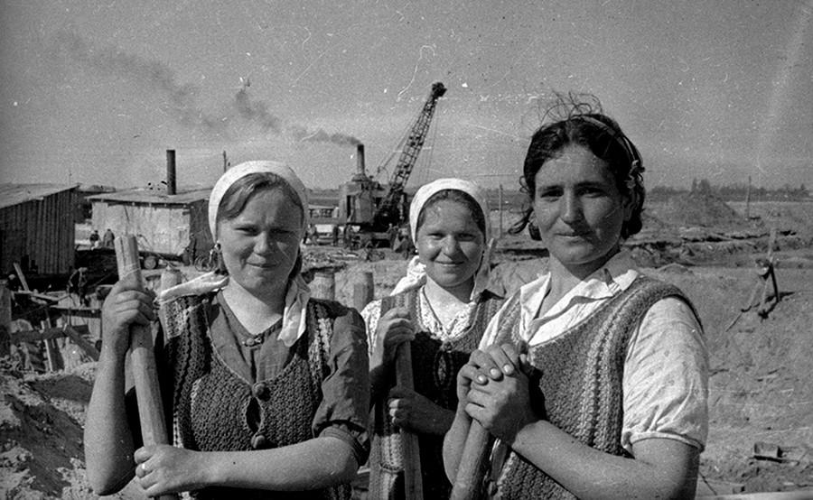 Para perempuan memegang sekop di lokasi pembangunan Kanal Dnieper-Bug.