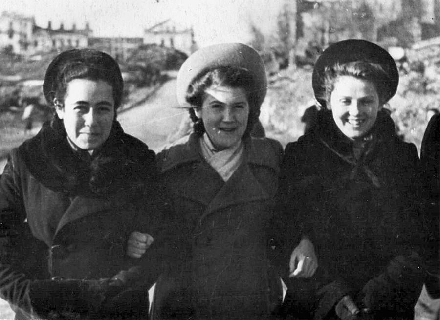 Para gadis teman satu kelas di jalanan Minsk yang hancur.