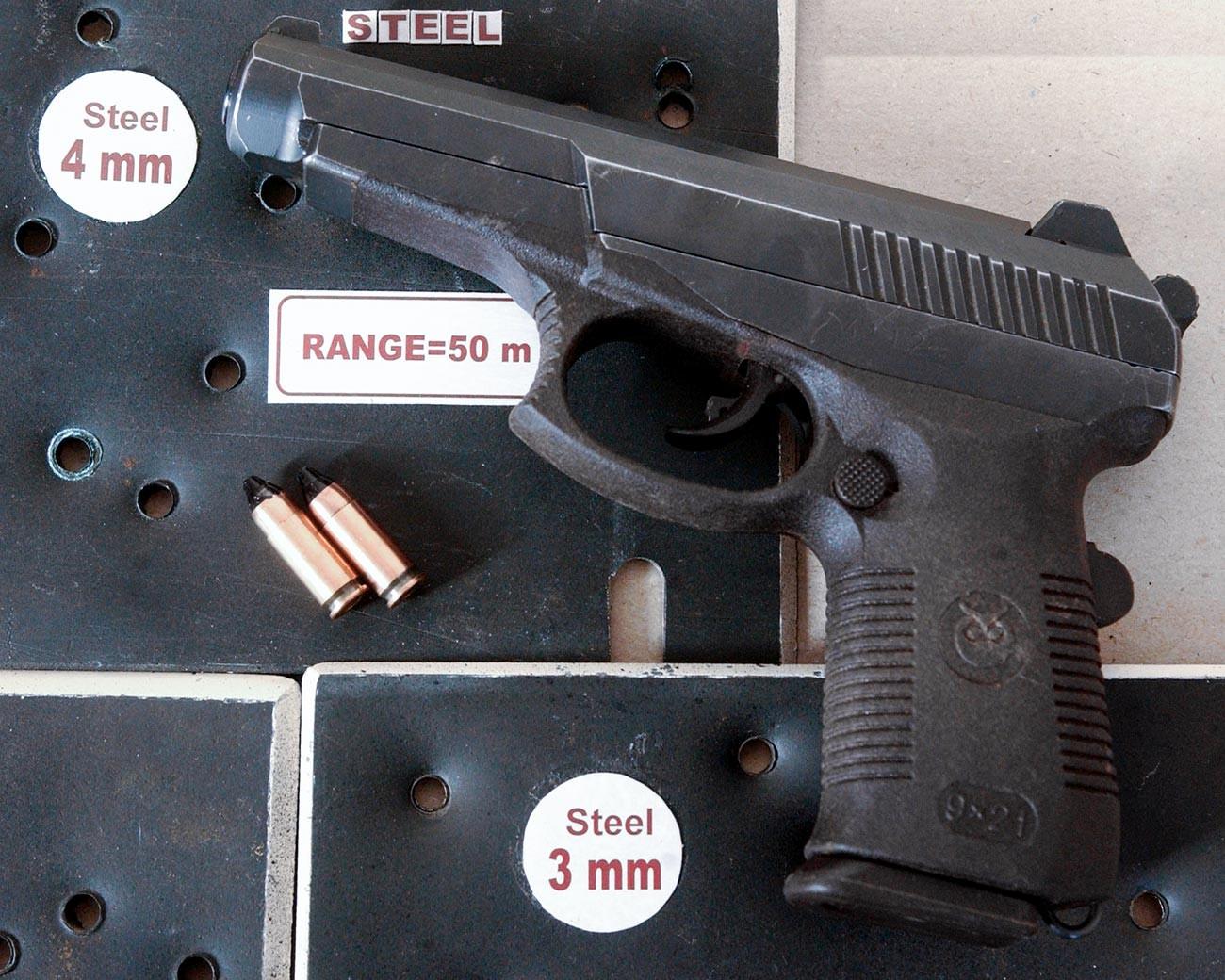Pištolj SR-1 (dizajniran u Središnjem znanstveno-istraživačkom institutu preciznog strojarstva). U pozadini su čelične ploče s rupama koje su napravili hici iz ovog pištolja.