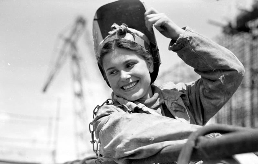 A female welder laughing