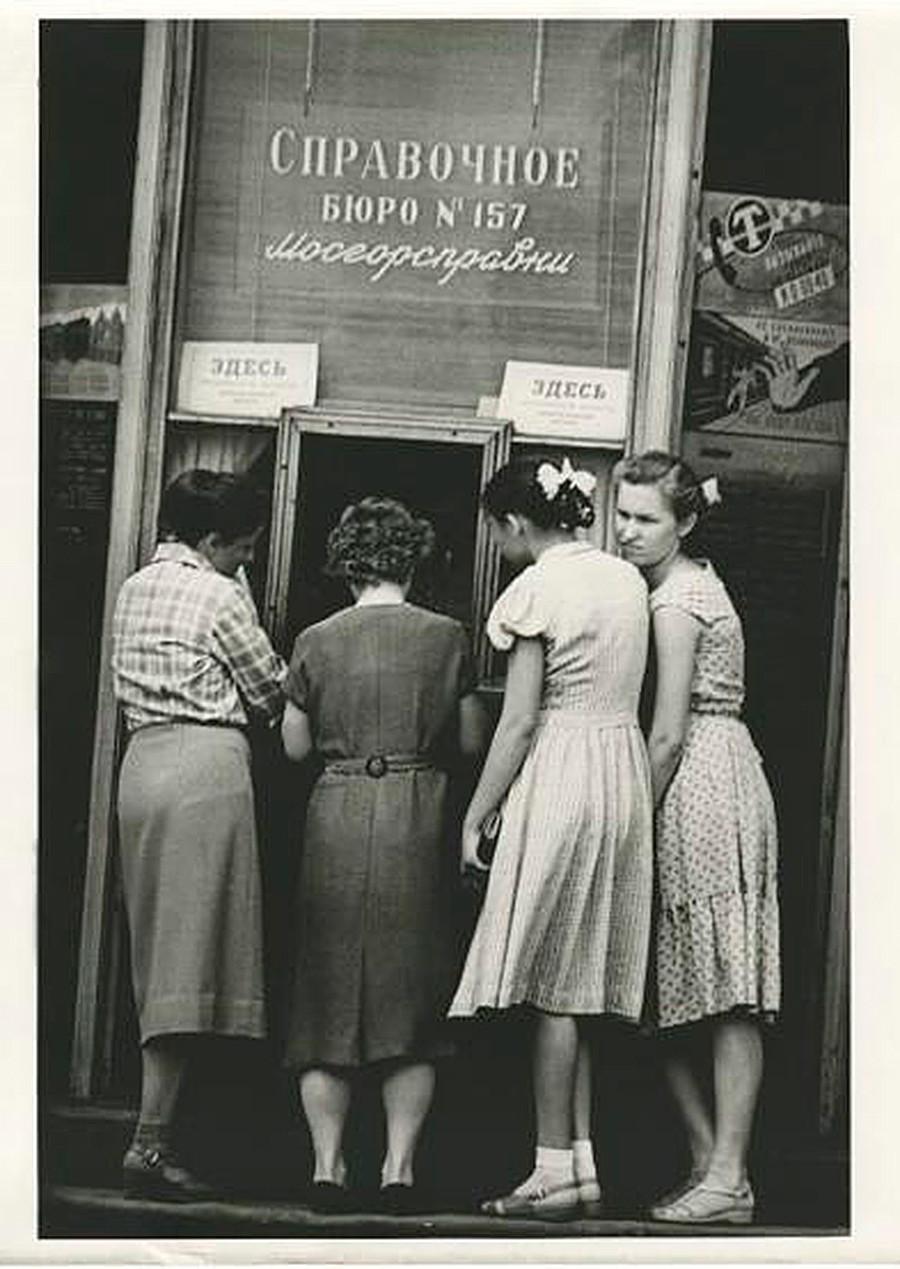 Beberapa perempuan mengantre di meja informasi.