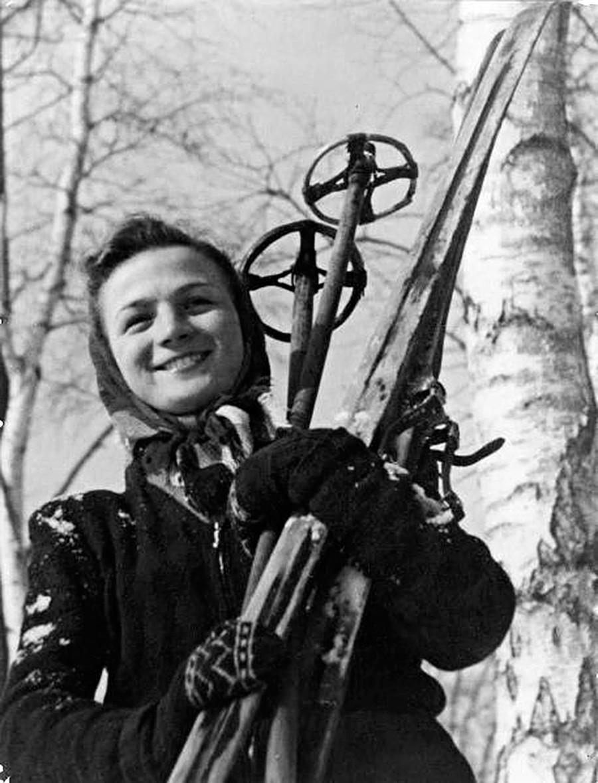 Seorang pemain ski perempuan berpose.