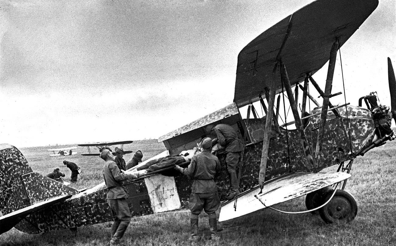 Vojaki nosijo ranjenega tovariša na letalo U-2 za polet v bolnišnico.