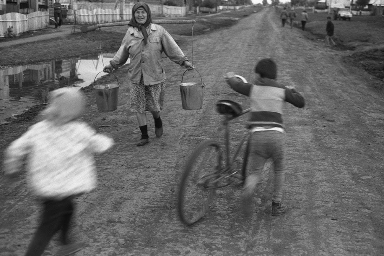 田舎道で自転車に乗る少年と天秤棒を持つ老女。1979年