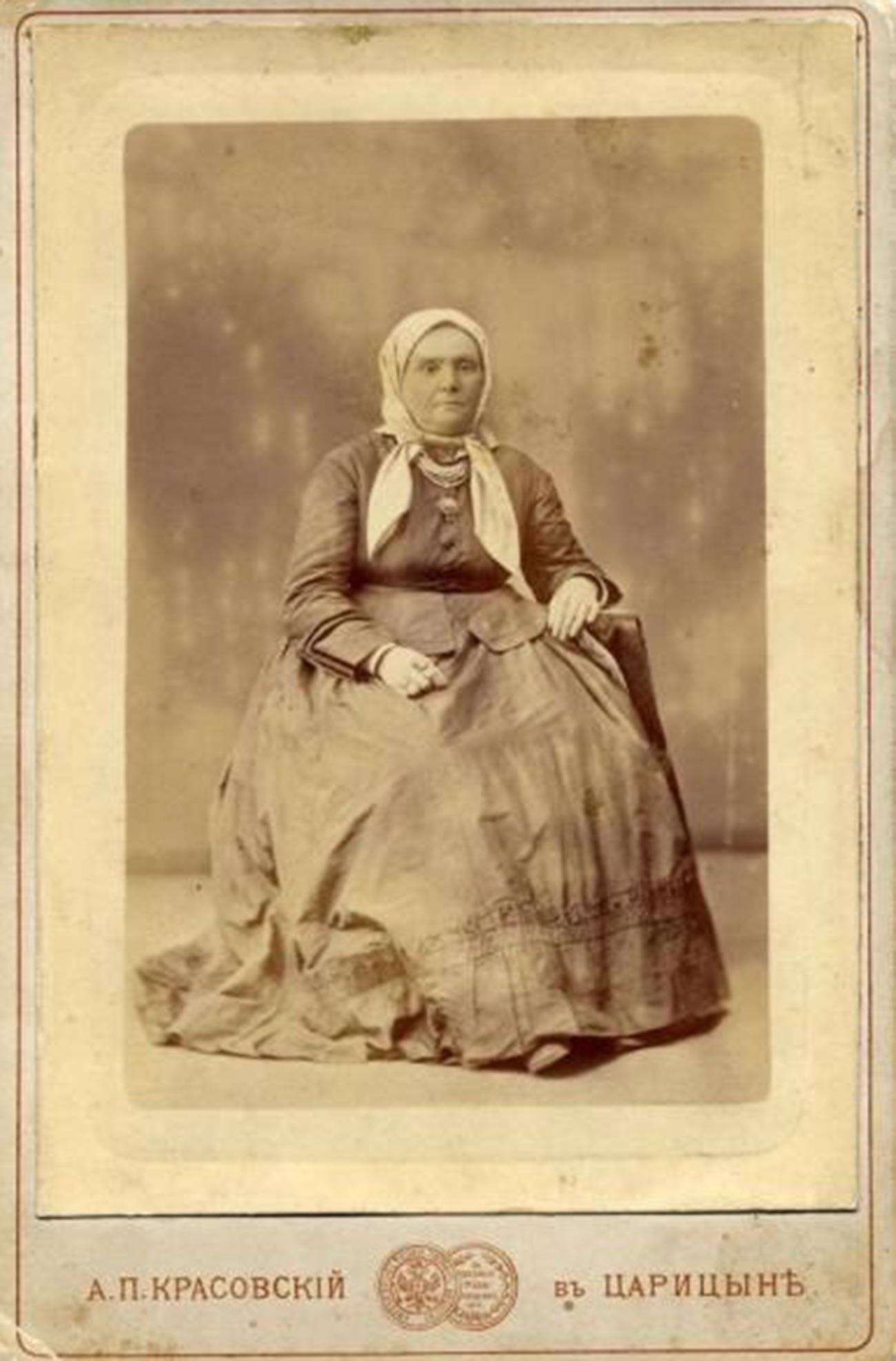 スカーフをかぶってポーズを取る老女。1870年代
