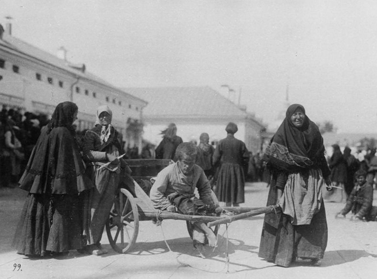 Женщина-крестьянка везет на тележке больного молодого человека у Саровского монастыря, 1903