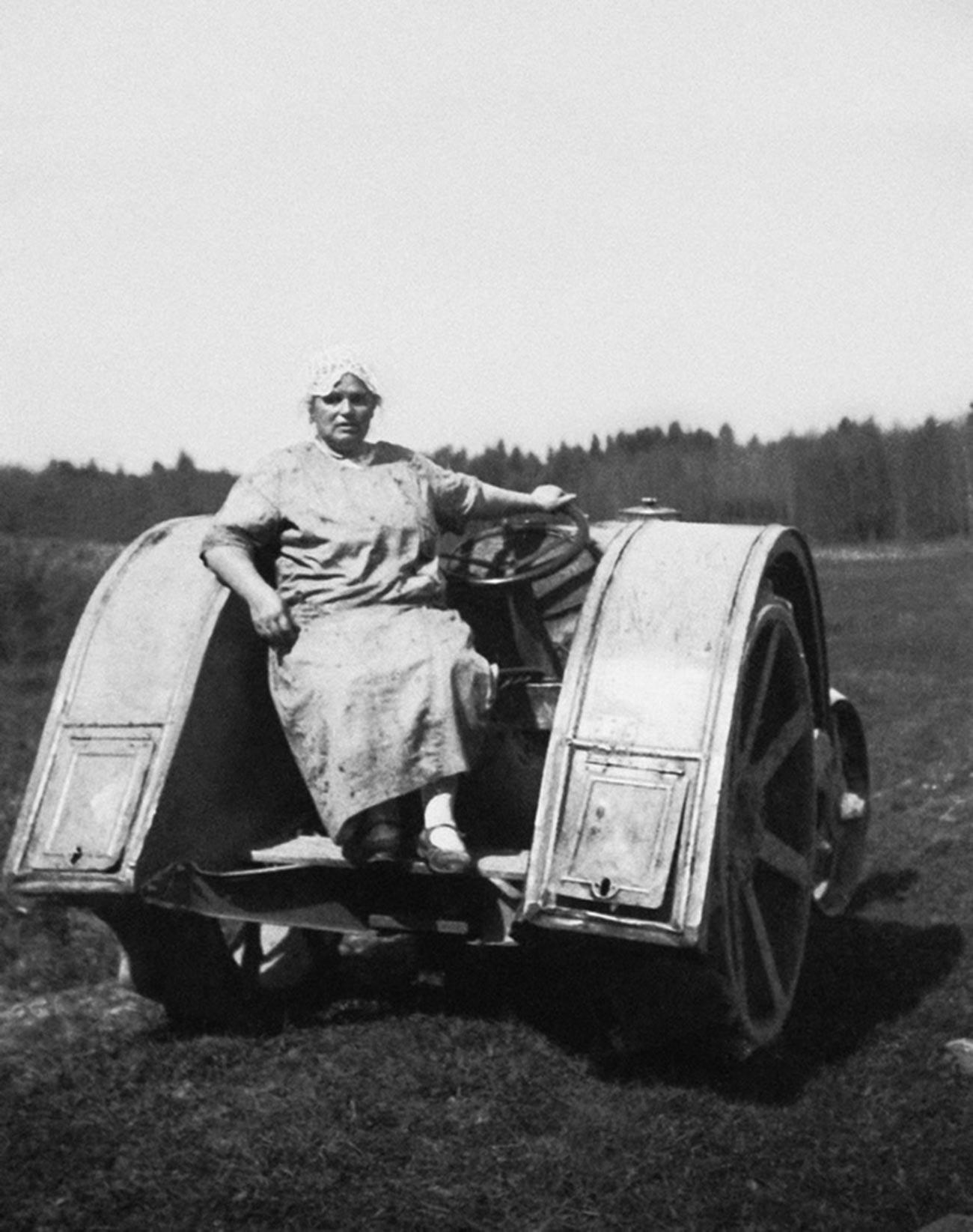 Seorang perempuan tua berpose di atas traktor.
