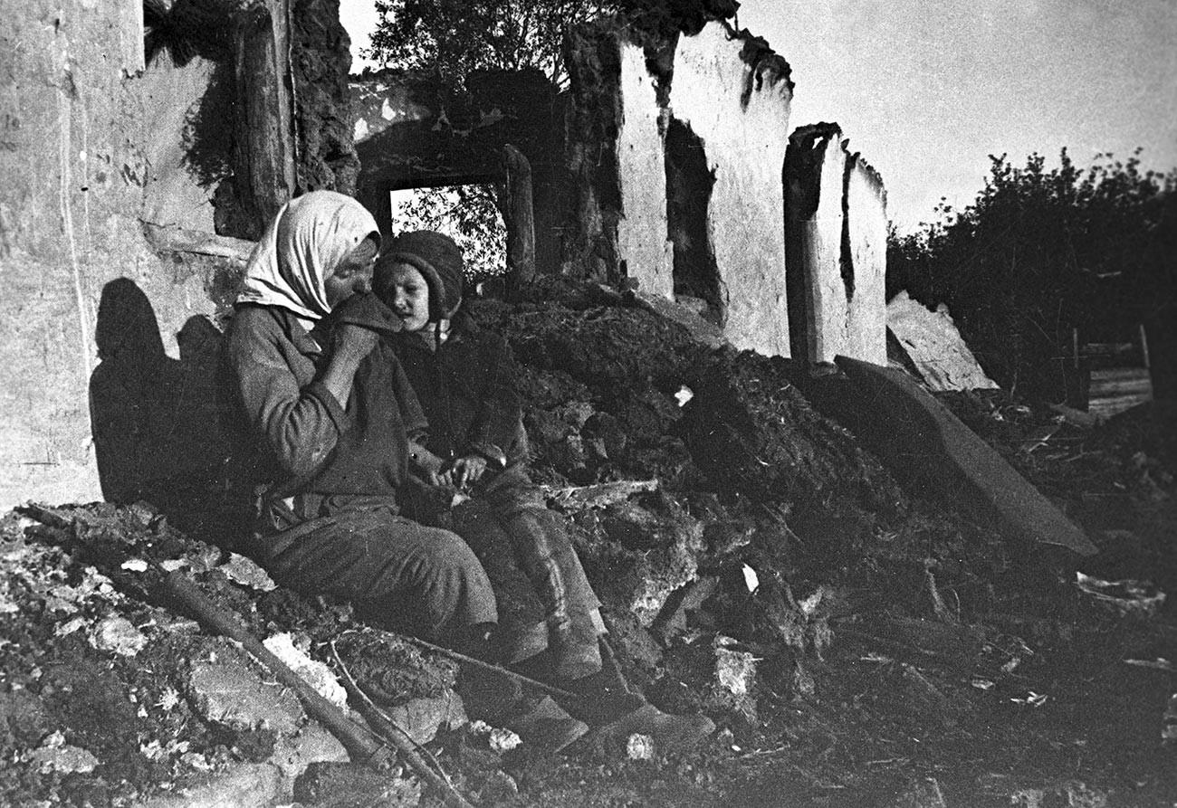 Anastassia Vetrenkova, employée de kolkhoze, avec son enfant sur les ruines de sa maison