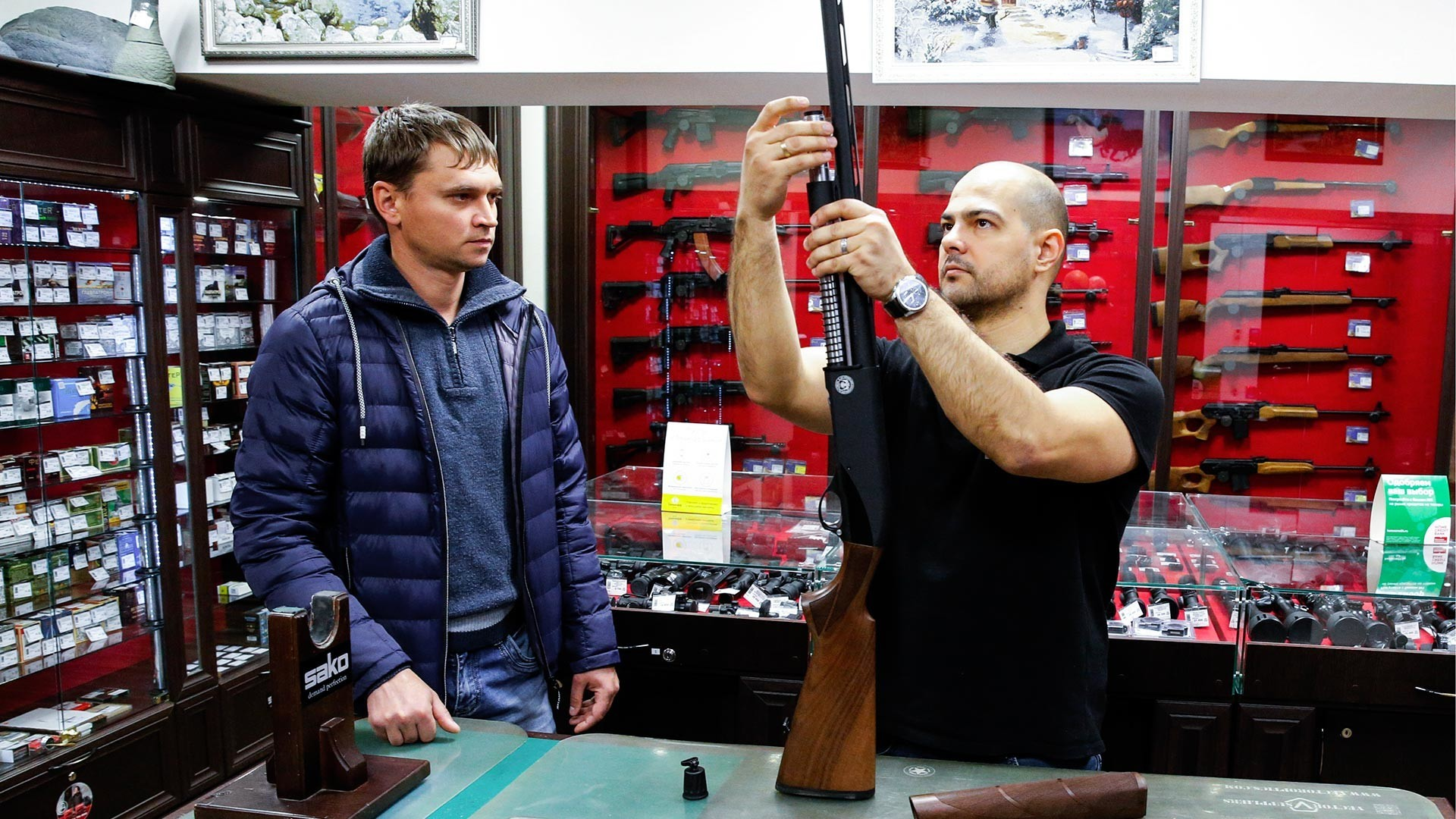 Stranka si ogleduje puške v prodajalni orožja v Čeljabinsku.