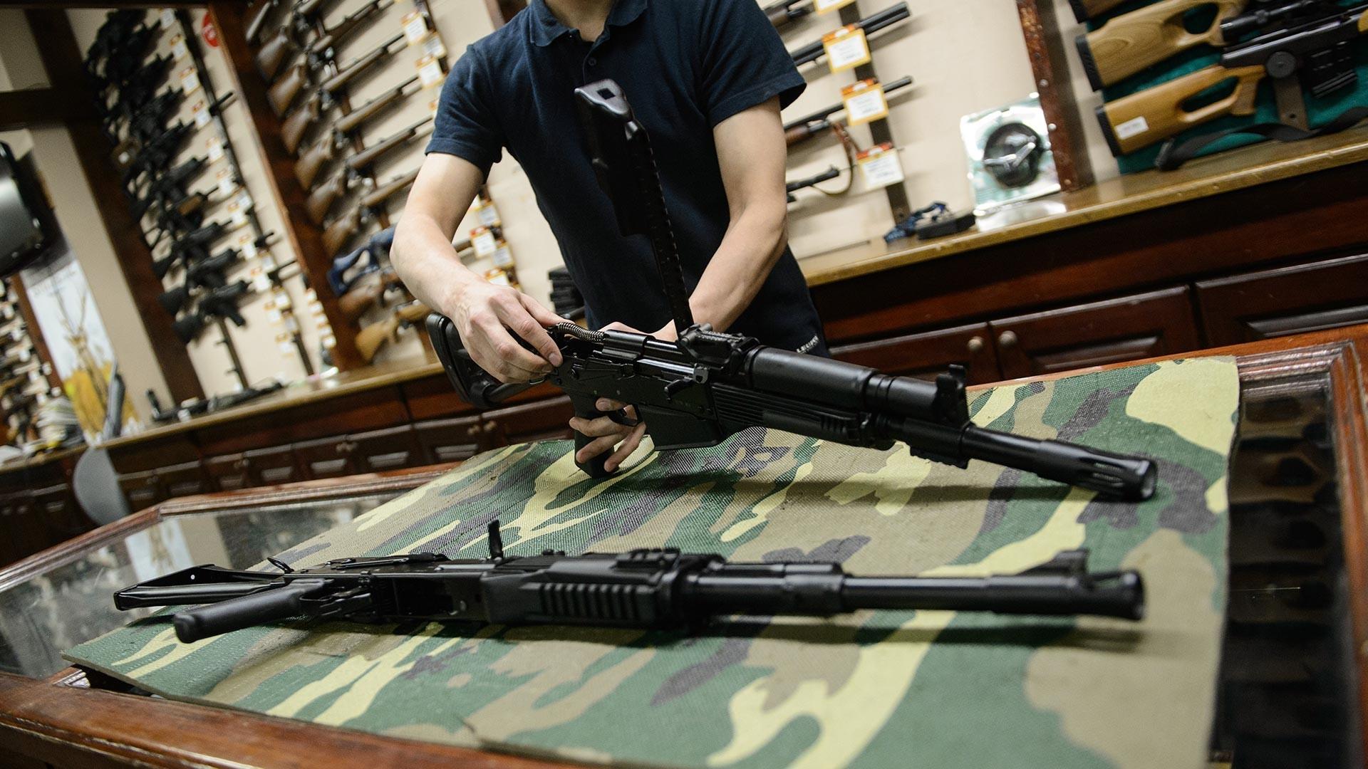 Pomočnik v prodajalni z orožjem v Čeljabinsku razstavlja puško.