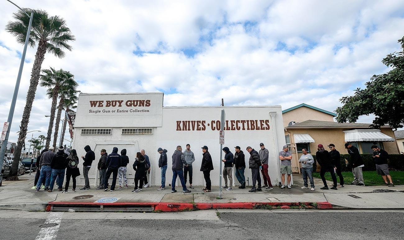 Ljudje stojijo v vrsti pred prodajalno z orožjem v Culver Cityju v Kaliforniji. Skrbi okoli koronavirusa so privedle do nakupovalne mrzlice tako v trgovinah z živili kot z orožjem. 15. marca, 2020.