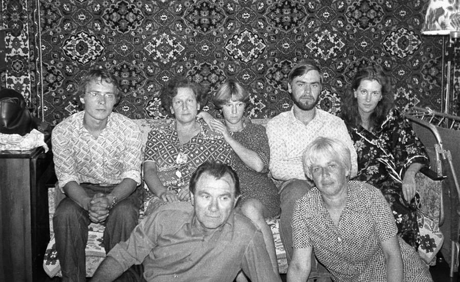 Ein erweitertes Familienporträt aus den 1980er Jahren mit einem typischen Wandteppich als Hintergrund