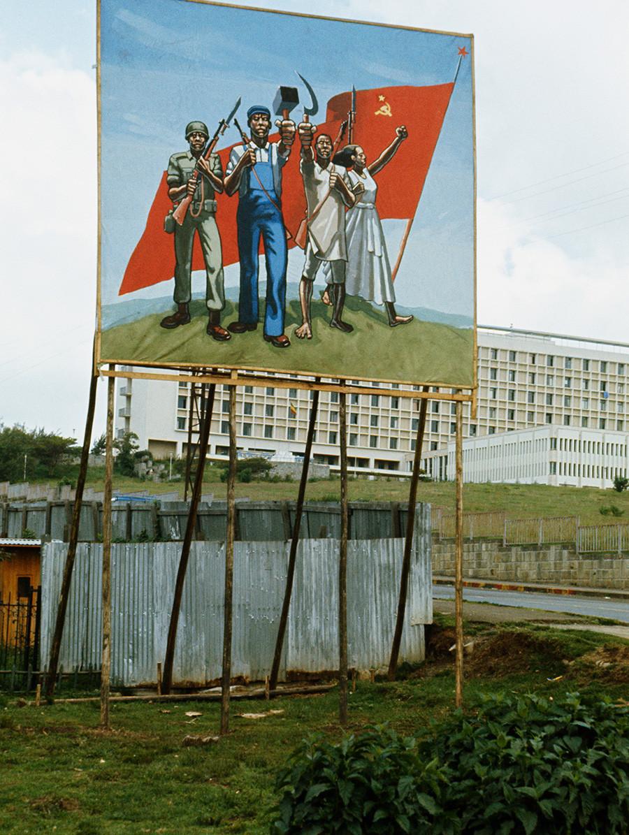 Пропаганден плакат показва няколко етиопци, които държат комунистически символи пред съветското знаме, в Адис Абеба, столицата на Етиопия, 1977 година
