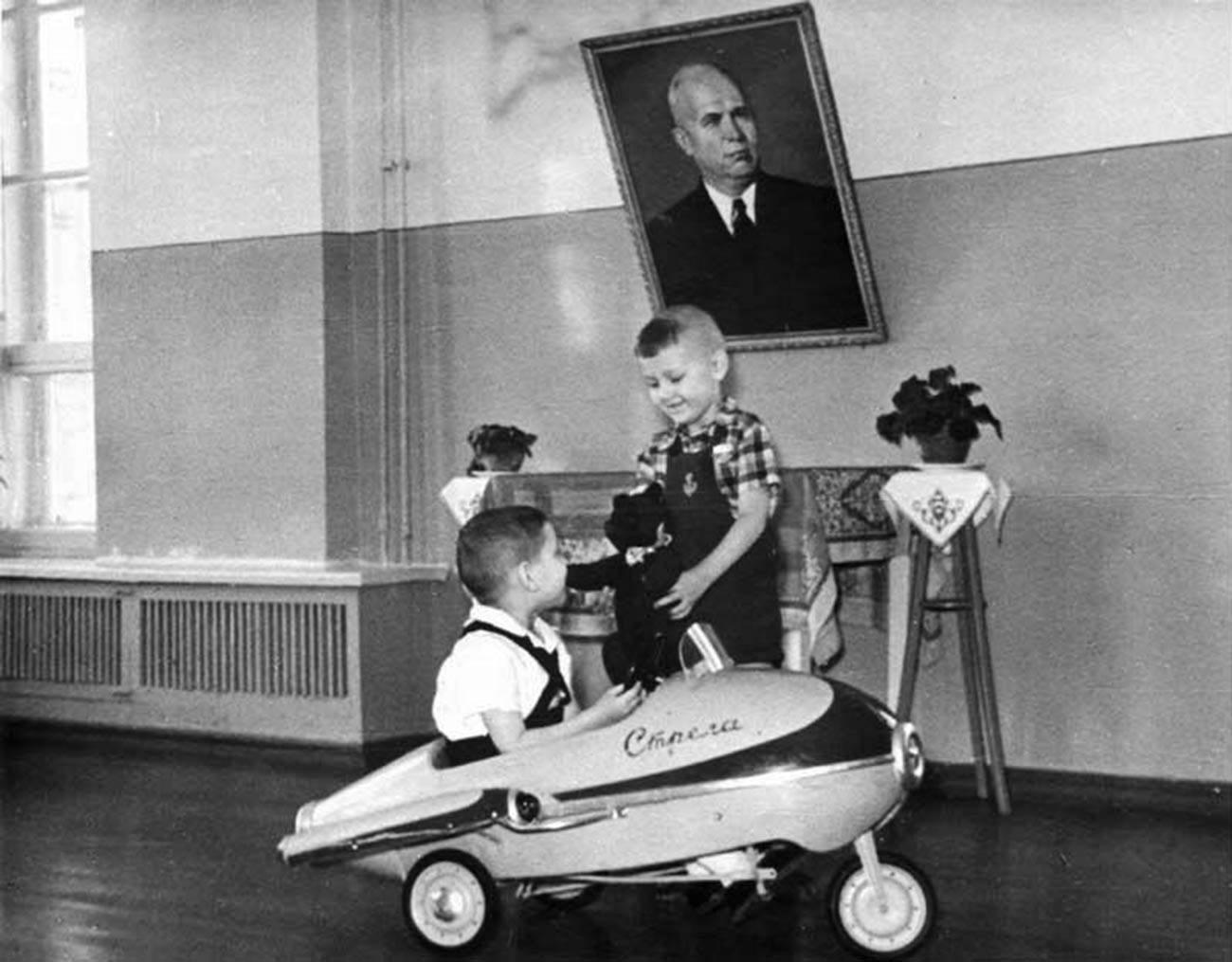 Niños jugando con un coche de pedales Strelá, 1962.