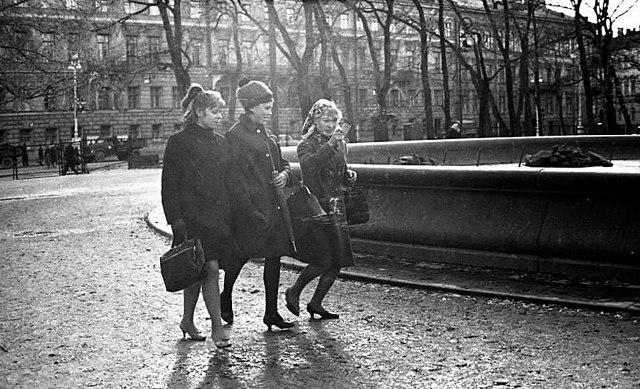 Tiga perempuan berjalan di taman.