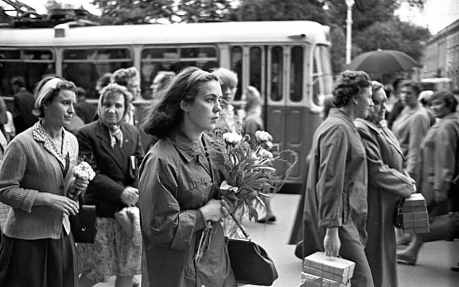 Perempuan membawa rangkaian bunga.