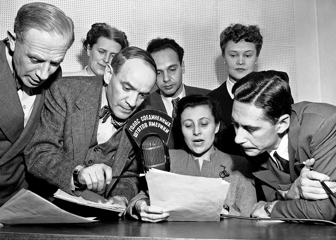 A group of State Department announcers huddle around the microphone after the initial shortwave broadcast in Russian to Russia from New York City on Feb. 17, 1947.