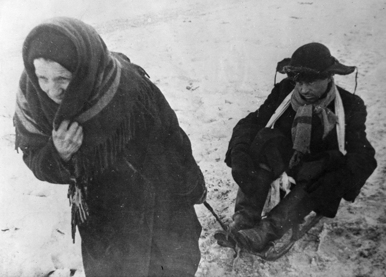 Ženska pelje na sankah moža, oslabelega zaradi lakote, v obleganem Leningradu med drugo svetovno vojno