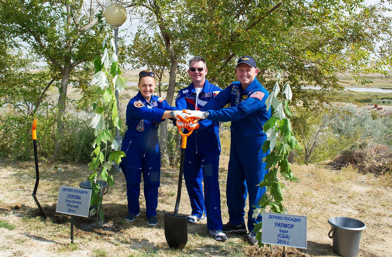 Les cosmonautes Alexandre Samokoutiaïev et Elena Serova et l'astronaute américain Barry Wilmore plantent des arbres au Centre spatial de Baïkonour, 2014