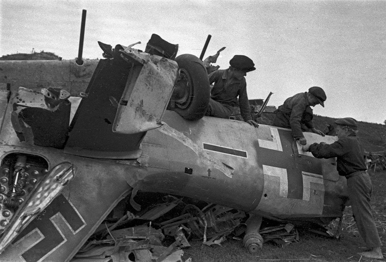 Unos niños examinan los restos de un caza Messerschmitt de los fascistas.