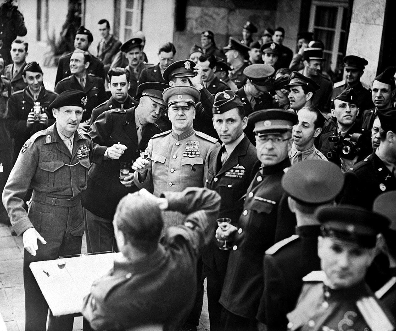 Британският фелдмаршал Бернард Монтгомъри (вляво), американският генерал Дуайт Айзенхауер и съветският фелдмаршал Георги Жуков, вдясно от Монтгомери. Британският въздушен маршал сър Артър Тедър (вдясно от Жуков)