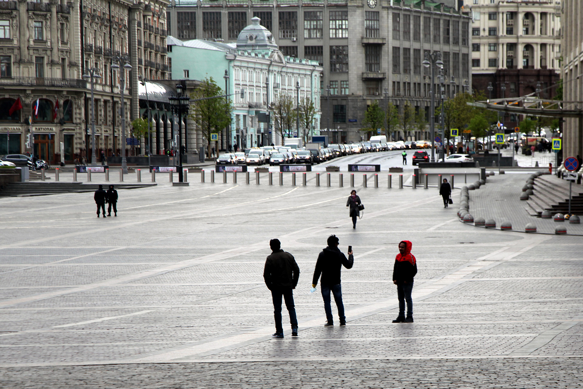 Orang asing mengambil gambar di kawasan Lapangan Manezhnaya, sementara di belakang mereka terlihat jejeran kendaraan di Tverskaya Ulitsa.