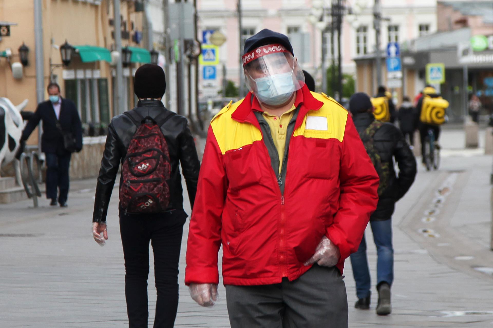Seorang pria mengenakan pelindung wajah saat berjalan di Klimentovskiy Pereulok, tidak jauh dari Stasiun Metro Tretyakovskaya.