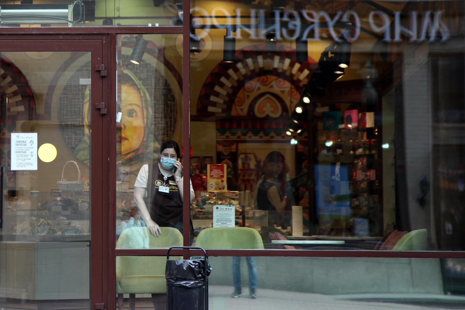 Seorang pekerja toko sedang berbicara di telepon di sebuah toko cokelat khas Rusia Alyonka, yang sepi pembeli di daerah Arbatskaya Ulitsa.