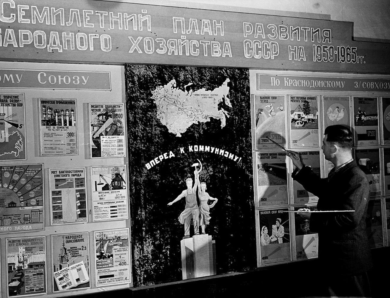 В зале Дома культуры совхоза «Краснодонский» помощник комбайнера Федор Фролов у семилетнего плана развития сельского хозяйства, 1959, Казахстан.