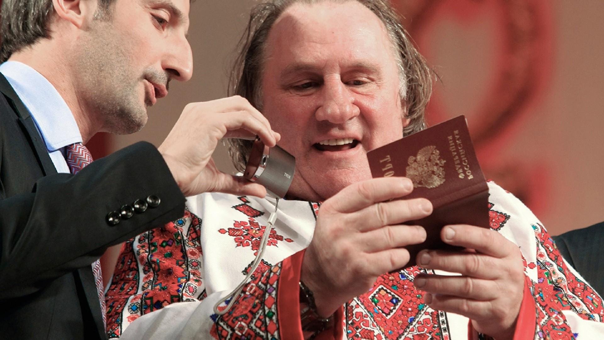 Gérard Depardieu, désormais détenteur de la citoyenneté russe, en tenue traditionnelle mordve, examine son passeport avec son traducteur, sur la scène du Théâtre d'opéra et de ballet de Saransk, capitale de la République de Mordovie où il possède un logement.