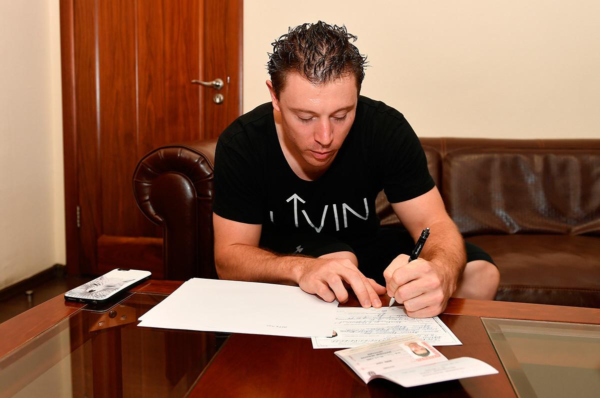 Le coureur cycliste australien Shane Perkins remplissant son formulaire de demande de la citoyenneté russe