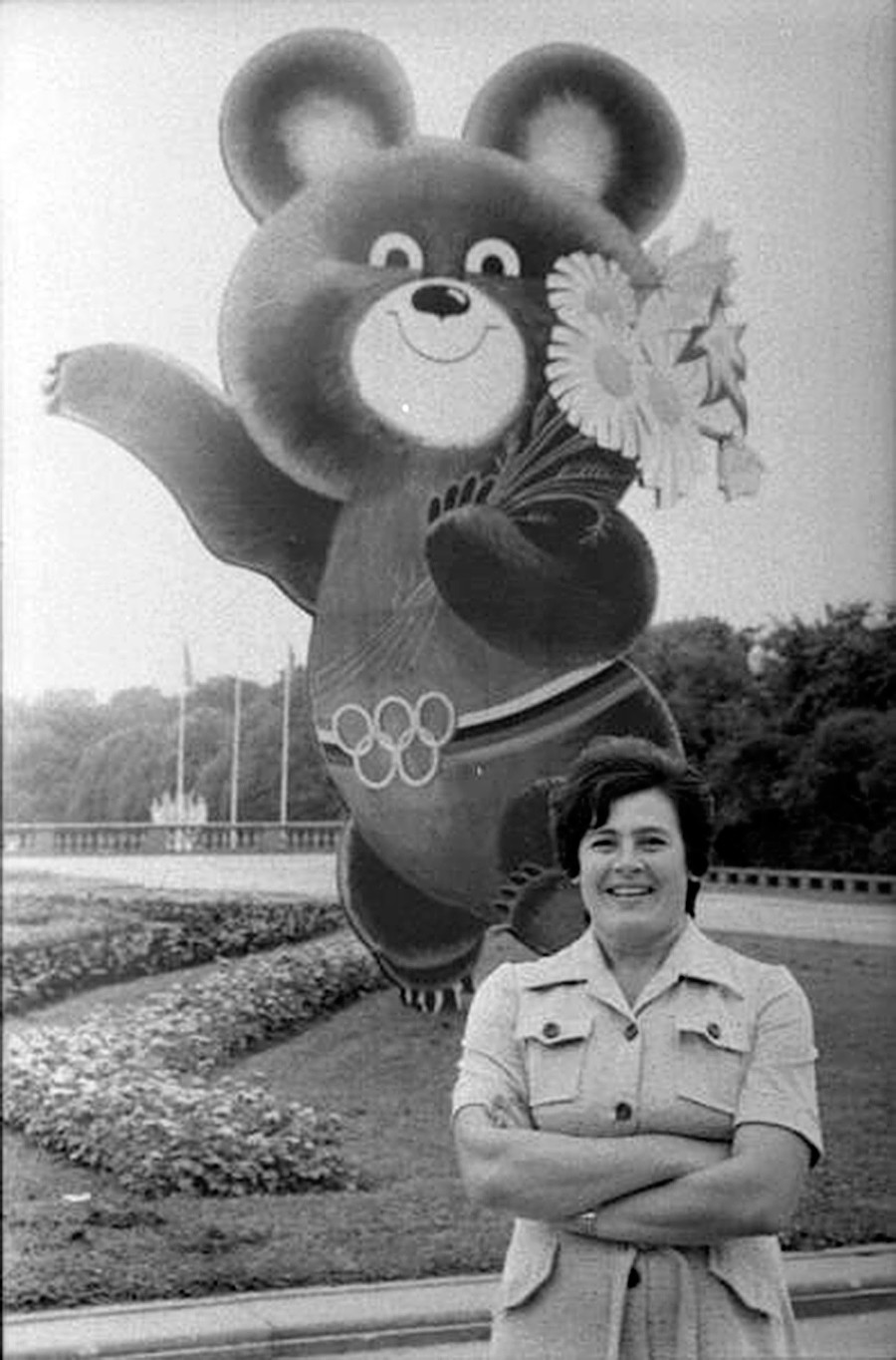 Portrait of a woman in front of Mishka, the mascot of the 1980 Moscow Olympics