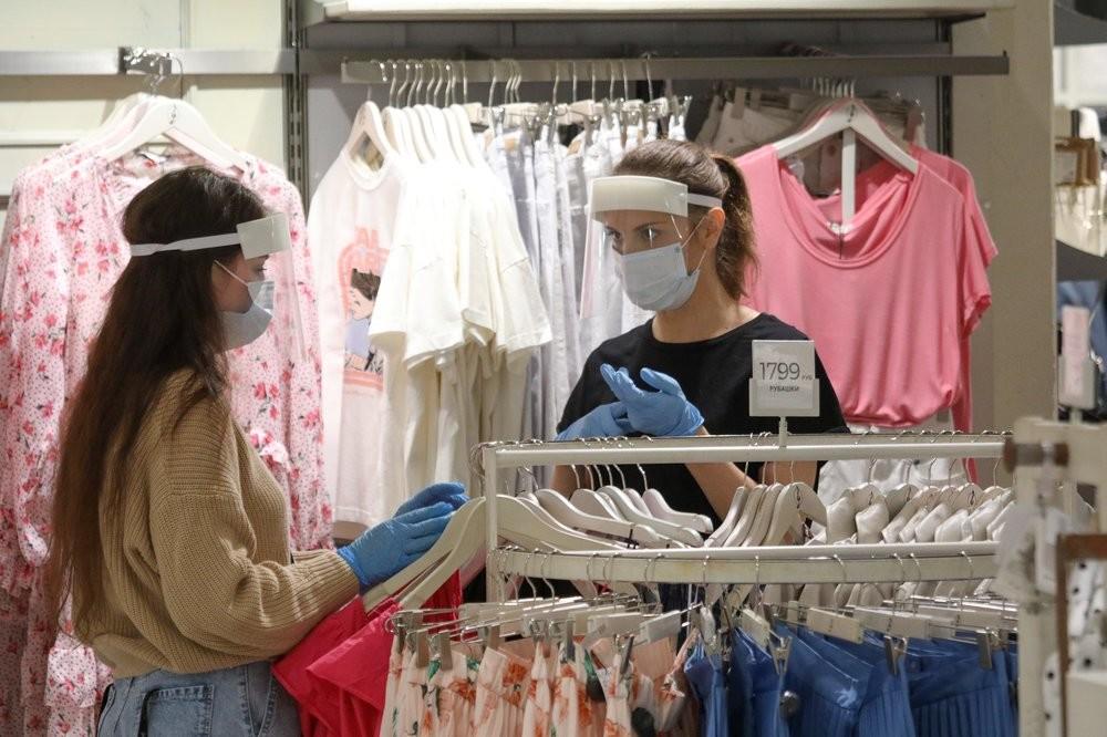 Pembeli dan karyawan toko pakaian mengenakan masker dan sarung tangan.