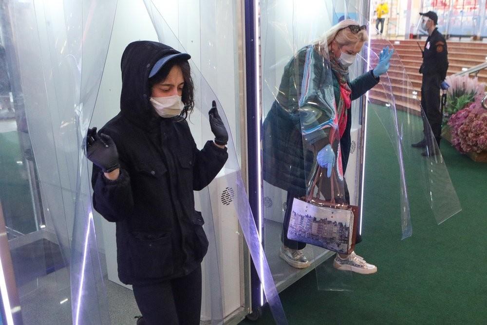 Pengunjung mal keluar dari bilik disinfeksi.