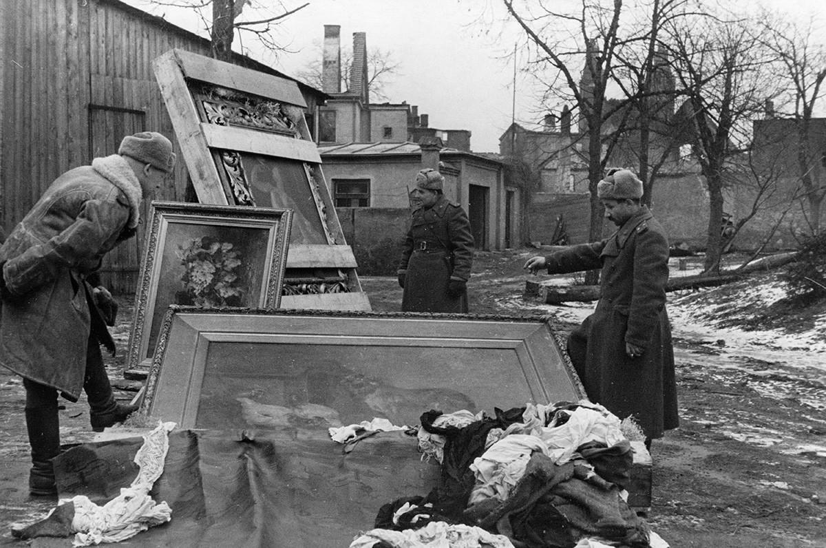 Soldaten der Roten Armee mit Gemälden, die 1945 von den Deutschen aus dem Palast Peterhof gestohlen wurden.