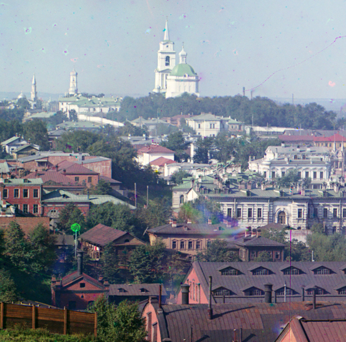 View of central Perm from City Hills. In distant background from left: minaret of Main Mosque, bell tower of Trinity Cathedral. Center: Transfiguration Cathedral. Center far right: side & back of Meshkov House. All buildings linked by Monastery Street. Summer 1909.